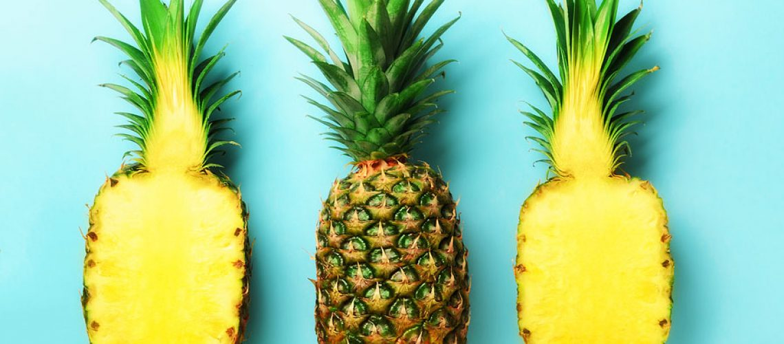 Bright pineapple pattern for minimal style. Top View. Pop art design, creative concept. Copy Space. Fresh pineapples on blue background